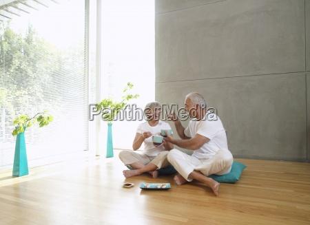 senior couple sitting on wooden floor