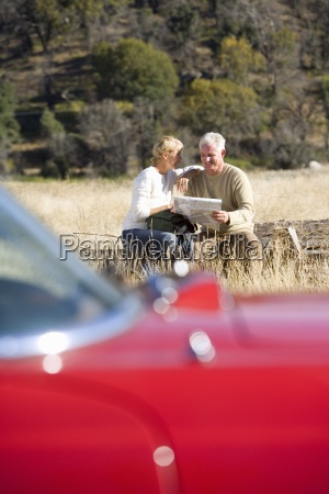 senior couple look at map in