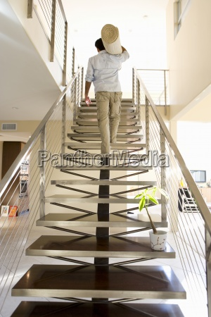 man carrying rolled carpet up stairs