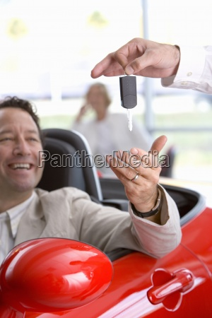 salesman handing man keys to new