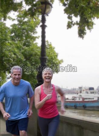 mature couple running on waterfront
