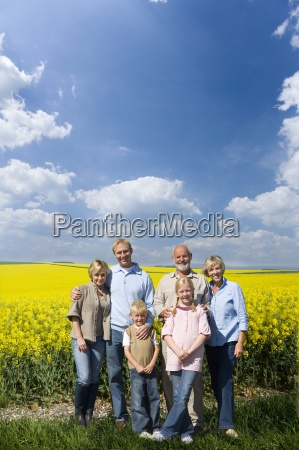 multi generational family standing in field