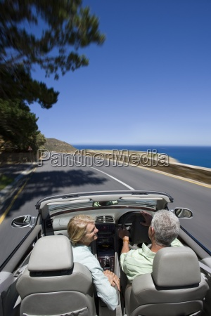 couple driving convertible on coast highway