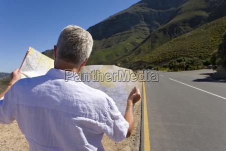 man looking at map on remote