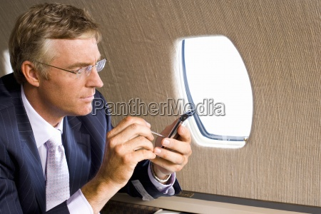 businessman using electronic organiser on aeroplane