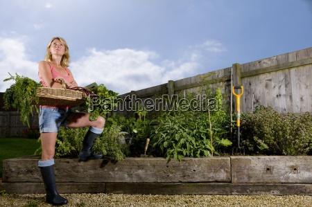 woman standing in organic garden holding