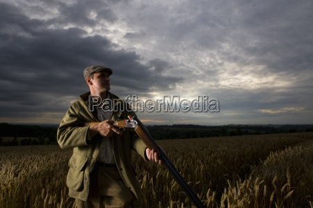 hunter with rifle standing in wheat