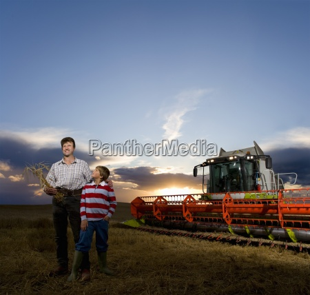 farmer and son standing next to