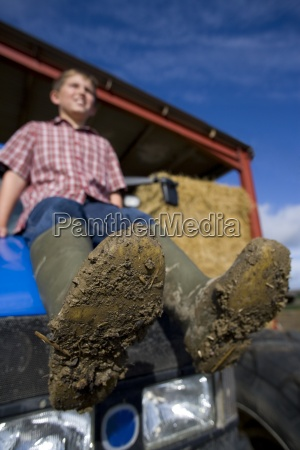 boy sitting on tractor with muddy