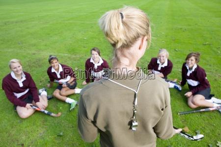 coach standing before teenage girl field