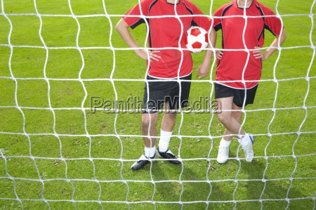 soccer players standing at goal net