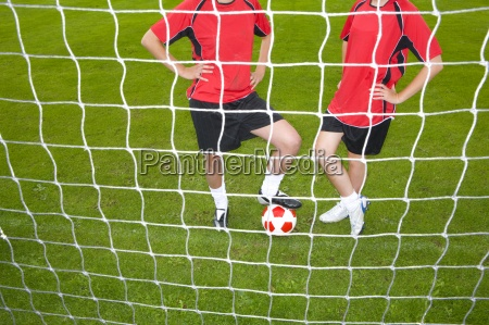 soccer players standing with ball at