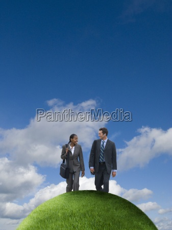 business people reaching hilltop
