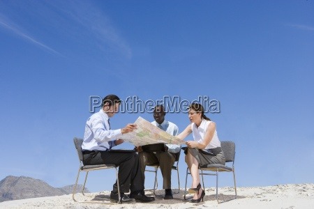 business people looking at map in