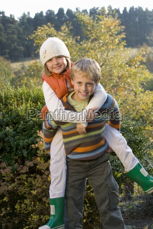 portrait of brother piggybacking sister