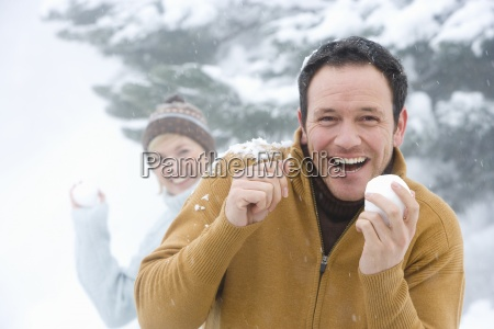 mid adult couple having snowball fight