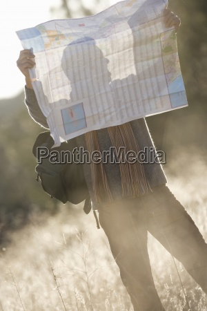 hiker in field looking at map