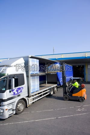 worker driving forklift loading inventory on