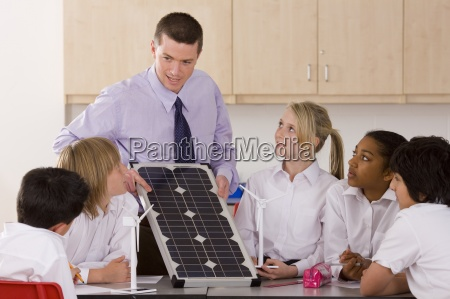 students listening to teacher explaining solar