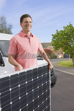man carrying solar panel across street