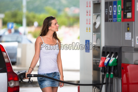 attractive young woman refueling her car