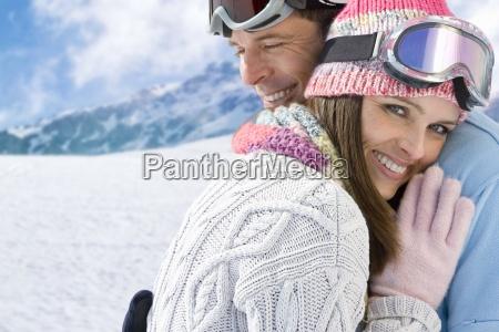 smiling couple in ski wear hugging