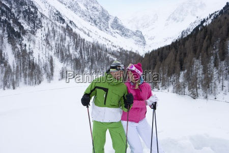 smiling skiers standing in valley ski