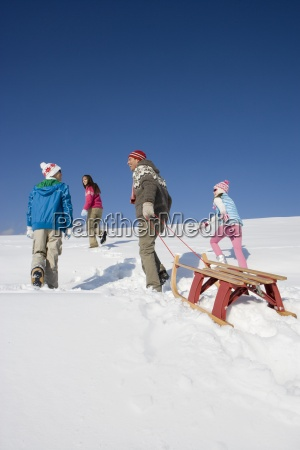 father walking uphill pulling sled with