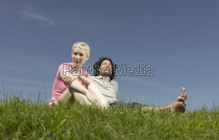 a couple sitting on the grass