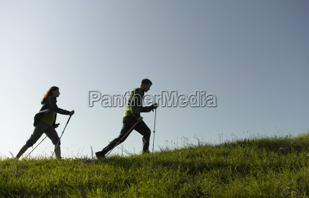 a couple out hiking using walking