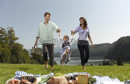 parents walking through the grass lifting