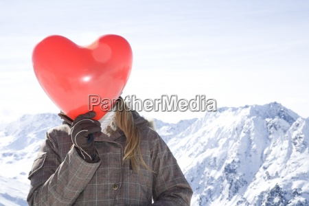 young woman holding red heart shaped