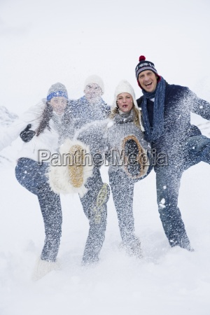 two young couples kicking snow in