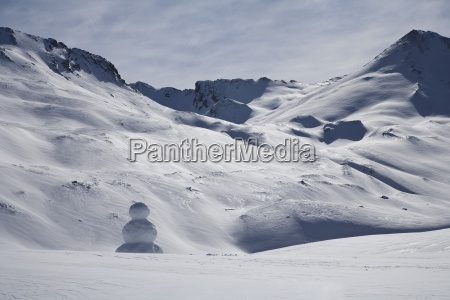 snowman in snow capped mountains of