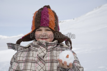 portrait of young girl holding snowball