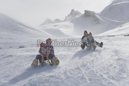 young family sledding down mountain on