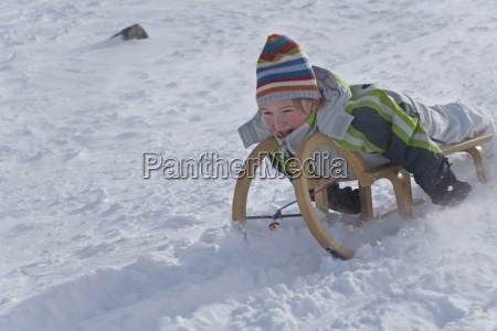 young boy sledding in snow on