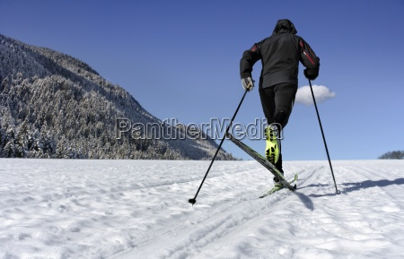 mid adult man cross country skiing