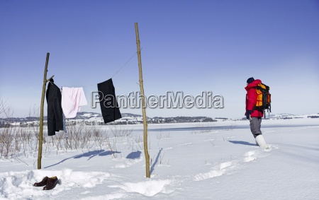 mid adult businessman backpacking through snow