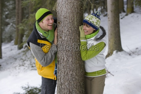smiling couple leaning against tree trunk