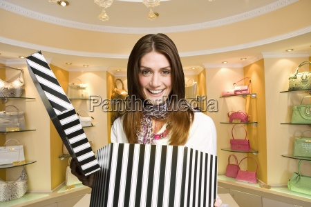 excited woman opening hat box in