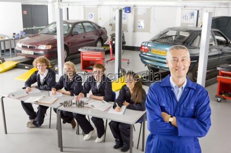 teacher with students studying automotive trade