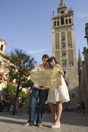 young couple looking at tourist map