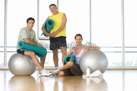 two men and woman with exercise