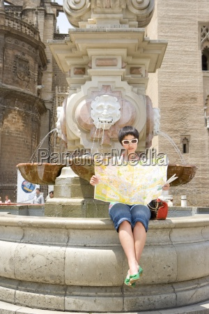 woman in sunglasses reading map by