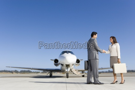 businessman and woman with briefcase shaking