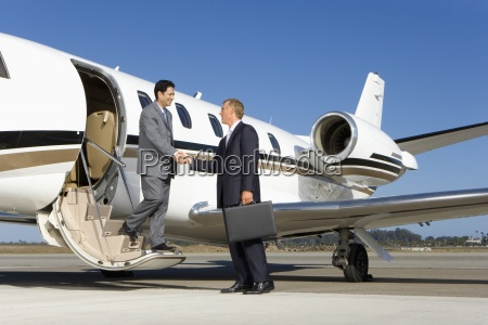 businessman boarding aeroplane on runway shaking