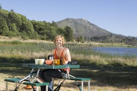 woman at portable table by lake