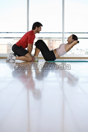 man helping woman with sit ups
