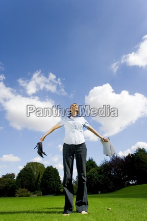 woman on grass holding out paperwork